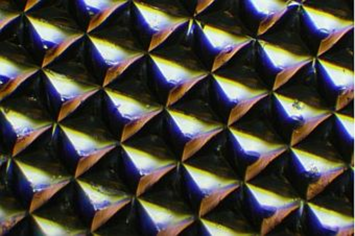 Microscopic image of a silk optical implant created when purified silk protein is poured into molds in the shape of multiple micro-sized reflectors and then air-dried