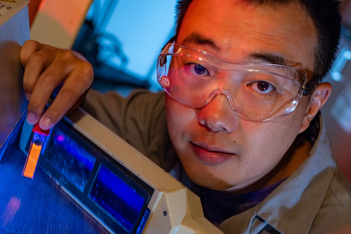Rice graduate student Bo Jiang shows a fluorescing vial of soluble amyloid beta peptide aggregates implicated in the onset of Alzheimer's disease. The peptides are tagged and tracked with a ruthenium complex developed at Rice University that can monitor them in lab experiments as they grow over time.