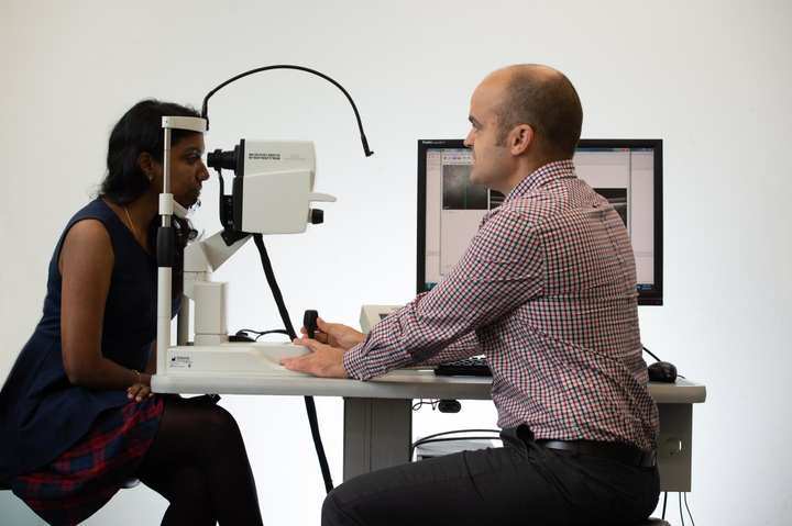 QUT researcher David Alonso-Caneiro with an OCT scanner in QUT's School of Optometry and Vision Science.